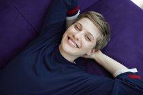 Retrato de una mujer rubia, acostada en un sofá — Stock Photo