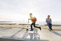 Father watching son riding scooter on beach promenade at sunset — Stock Photo