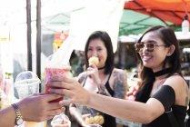 Donna che compra un frullato da un venditore ambulante in Thailandia — Foto stock