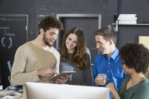 Smiling coworkers sharing tablet in office — Stock Photo