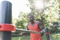 Юный спортсмен тренируется на параллельных барах, на открытом воздухе — стоковое фото