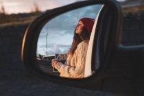 Island, junge Frau mit Kaffee zu gehen bei Sonnenuntergang, in Flügelspiegel gespiegelt — Stockfoto