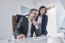 Empresário sorridente e mulher de negócios olhando para o computador na mesa no escritório — Fotografia de Stock