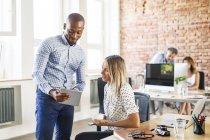 Бізнесмен показує планшет з колегою на столі в офісі — стокове фото