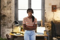 Portrait of smiling young woman standing front of desk in a loft — Stock Photo