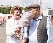 Старшая пара на ярмарке наслаждается сладкой ватой — стоковое фото