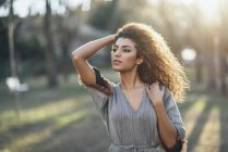 Portrait of young woman in a park at evening twilight — Stock Photo