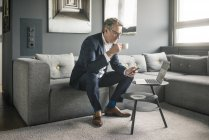 Mature businessman with cup of coffee and laptop using cell phone on couch — Stock Photo