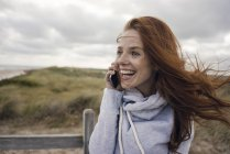 Redheaded woman using smartphone on the beach — Stock Photo