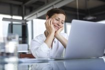 Smiling businesswoman sitting at glass table in office looking at laptop — Stock Photo