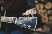 Jovem mulher afinação guitarra, close-up — Fotografia de Stock