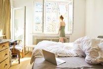 Vue arrière de la femme dans la chambre à coucher regardant par la fenêtre — Photo de stock