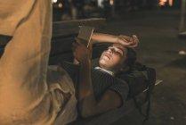 Jeune femme couchée sur le banc la nuit en utilisant un téléphone portable — Photo de stock