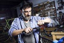 Человек работает на велосипеде в мастерской — стоковое фото