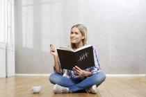 Портрет улыбающейся блондинки с книгой на полу — стоковое фото