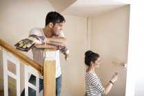 Young couple refurbishing new home, painting staircase — Stock Photo