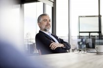 Впевнений бізнесмен, який сидить за столом у офісі і думає — стокове фото