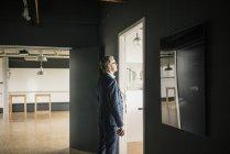 Hombre de negocios serio maduro de pie en el pensamiento de la oficina - foto de stock