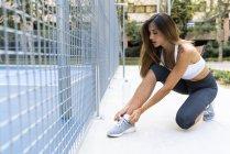Sportive jeune femme attacher ses chaussures avant l'entraînement — Photo de stock