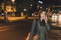 Ritratto di giovane donna d'affari con borsa in pelle al telefono di notte — Foto stock