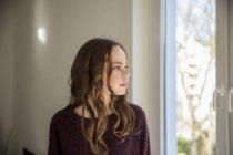 Дівчинка-підліток дивиться з вікна, мріяти — стокове фото