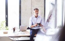 Улыбающийся зрелый бизнесмен сидит на столе в офисе и использует контроллер — стоковое фото