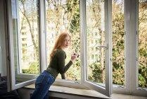 Porträt einer lächelnden rothaarigen Frau, die sich aus dem Fenster lehnt — Stockfoto