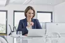 Businesswoman using laptop at desk in office — Stock Photo