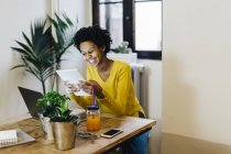 Young african american woman sitting at table with several portable devices — Stock Photo