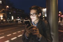 Homme d'affaires souriant utilisant un téléphone portable dans la rue urbaine la nuit — Photo de stock