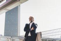 Усміхнений зрілий бізнесмен в місті на стільниковий телефон — стокове фото