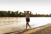 Jovem mulher andando descalça na beira do rio — Fotografia de Stock