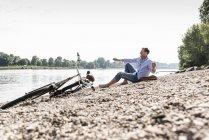 Homme mûr avec vélo au bord du Rhin — Photo de stock