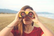 Donna con binocolo sulla spiaggia — Foto stock