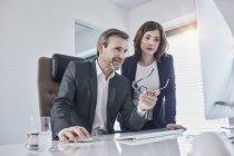 Empresário e mulher de negócios discutindo na mesa no escritório — Fotografia de Stock