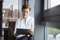 Бізнесжінка сидить в офісі у вікні за допомогою планшета — стокове фото