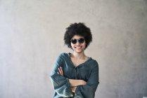 Ritratto di giovane donna sorridente che indossa occhiali da sole — Foto stock