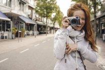 Рыжая женщина с аналоговой камерой — стоковое фото