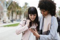 Испания, Барселона, две счастливые женщины смотрят на мобильный телефон на набережной — стоковое фото