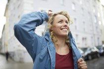 Portrait de femme blonde souriante revêtue de sa capuche — Photo de stock