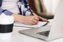 Крупним планом жінки з ноутбуком беручи відзначає на столі — стокове фото