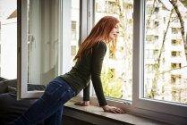 Donna rossa che guarda fuori dalla finestra — Foto stock