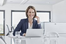 Portrait of smiling businesswoman using laptop at desk in office — Stock Photo
