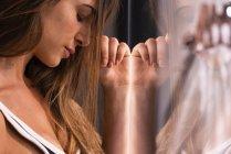 Серйозний привабливий молодої жінки з закритими очима спираючись на скло області — стокове фото