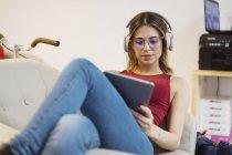 Случайная молодая женщина с наушниками с помощью планшета в коворкинг пространстве — стоковое фото