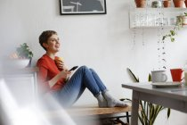 Женщина сидит на кухне, пьет кофе и проверяет сообщения со смартфона — стоковое фото