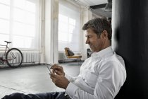 Hombre maduro sentado en el suelo usando el teléfono inteligente en el piso del loft - foto de stock