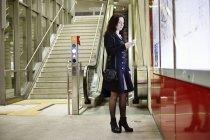 Germania, Colonia, giovane donna che guarda il suo cellulare nella stazione della metropolitana — Foto stock