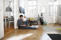 Man sitting in foor, using laptop, working from home — Stock Photo