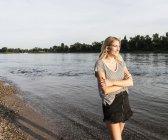 Donna bionda sul lungofiume la sera — Foto stock